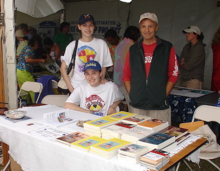 "Interns Lacey and Emily Farm at Koa Books' display table, with publisher Arnie Kotler, at the first ""More Fish in the Sea"" Festival, at Maui Community College."